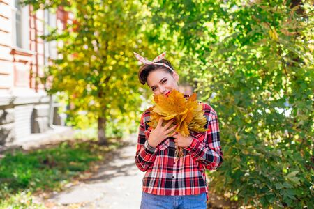 Beautiful woman with make up and hair in pin up style holding big bouquet of maple yellow leaves in a sunny autumn day.
