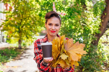 Beautiful woman with make up and hair in pin up style holding big bouquet of maple yellow leaves and black cup of coffee to go in a sunny autumn day. Copy space.