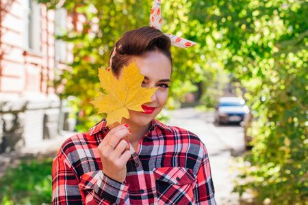 Beautiful woman with make up and hair in pin up style standing on the street, holding yellow maple leaf close to her face. Smiling woman outdoors Foto de archivo