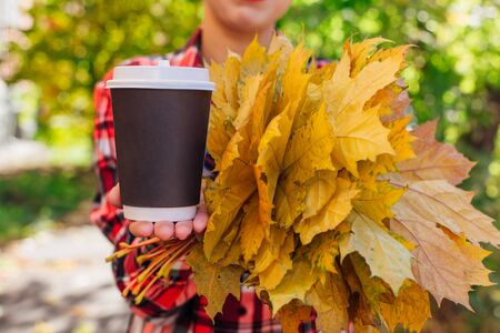 Close up black cup of coffee to go and bouquet of maple yellow leaves in a hand of a beautiful woman in a sunny autumn day. Copy space.