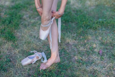 Ballerina standing on the grass and puts on pointes on her legs outdoors.