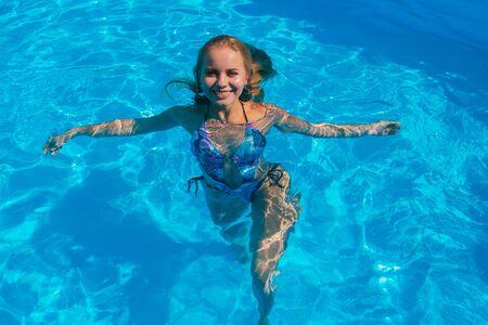 Mode portrait de belle jeune femme dans la piscine à l'extérieur. Belle femme nageant dans une piscine