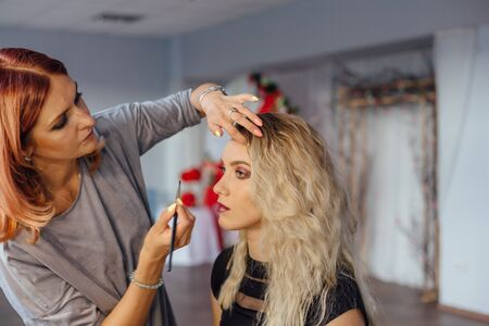 Make-up artist working with model in studio. Banque d'images
