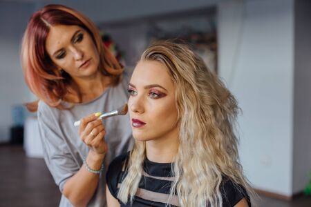 Make-up artist working with model in studio.