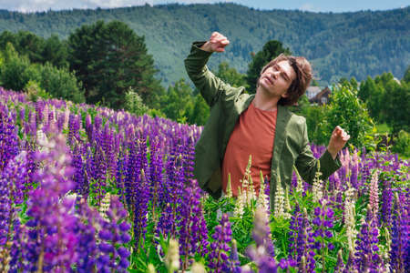 Tall handsome man in a green jacket standing and dancing on lupine flowers field, enjoing the beauty of nature. Man surrounded by purple and pink lupines.