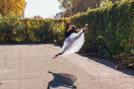 Woman ballerina in a white ballet skirt dancing in pointe shoes in a golden autumn park. Ballerina jumping doing a split