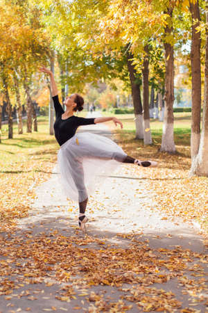Woman ballerina in a white ballet skirt dancing in pointe shoes in a golden autumn park. Ballerina standing in beautiful ballet pose on dry yellow leaves