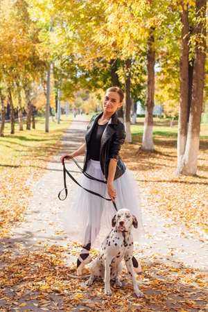 Ballerina with Dalmatian dog in the golden autumn park. Woman ballerina in a white ballet skirt and black leather jacket dancing in pointe shoes in autumn park with her spotty dalmatian dog. 免版税图像