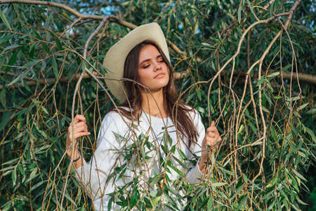 Beautiful brunette teenage girl dressed in a white sweater, jeans and cowboy straw hat standing behind tree brunches with green leaves