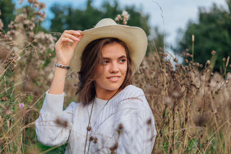 Beautiful brunette teenage girl dressed in a white sweater, jeans and cowboy straw hat sitting in dry brown bur grass, smiling and laughing during sunset