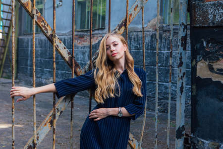 Close up portrait of a fashion look's woman with long blond hair standing near the old rusty gate. Young woman modern portrait.