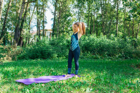 Woman walking with a yoga mat in a summer park wearing sports wear going to do some yoga exercises