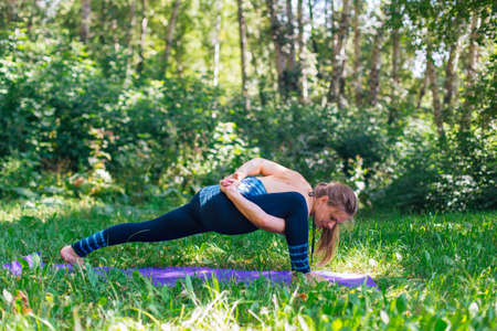 Young caucasian woman doing yoga exercises in summer city park. 免版税图像