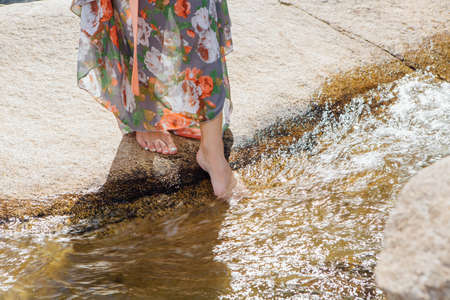 Woman with bare feet standing next to the running river with clear water, going to put a foot into the water