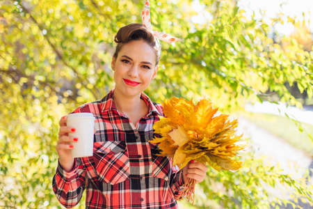 Beautiful woman with make up and hair in pin up style holding big bouquet of maple yellow leaves and white cup of coffee to go.