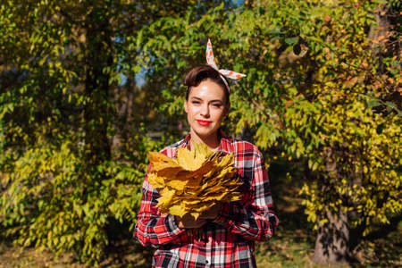 Beautiful woman with make up and hair in pin up style holding big bouquet of maple yellow leaves.