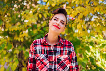 Beautiful woman with make up and hair in pin up style standing next to the autumn bush Фото со стока