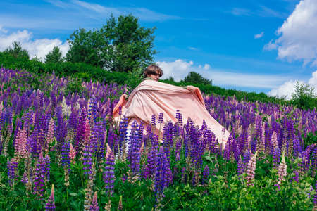 Tall handsome man standing on lupine flowers field with pink cloth