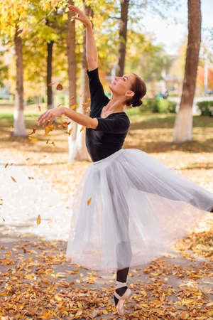 Woman ballerina in a white ballet skirt dancing in pointe shoes in a golden autumn park throwing up dry yellow leaves.