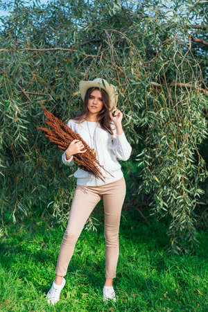 Happy beautiful brunette teenage girl dressed in a white sweater, jeans and cowboy straw hat standing behind tree brunches with green leaves holding dry bouquet