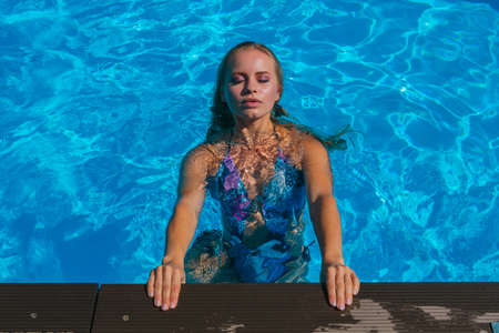 Fashion portrait of beautiful sexy young woman in swimming pool outdoors. Beautiful woman with long wet hair swimming in a pool