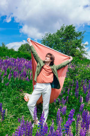 Tall handsome man in a green jacket standing on lupine flowers field with pink cloth, enjoing the beauty of nature. Man surrounded by purple and pink lupines.