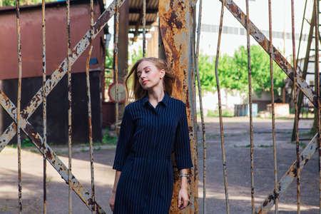 Fashion look's woman with long blond hair standing near the old rusty gate. Young woman modern portrait.