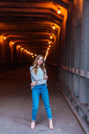 Young girl with long blond hair standing in a dark industrial tunnel with lights 免版税图像