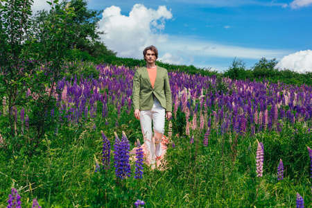 Tall handsome man in a green jacket walking on a pink cloth in lupine flowers field and enjoing the beauty of nature. Man surrounded by purple and pink lupines.