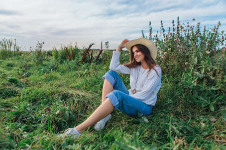 Beautiful brunette teenage girl dressed in a white sweater, jeans and cowboy straw hat sitting on green grass, smiling and laughing during sunset 免版税图像