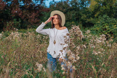 Beautiful brunette teenage girl dressed in a white sweater, jeans and cowboy straw hat standing in dry brown bur grass, smiling and laughing during sunset