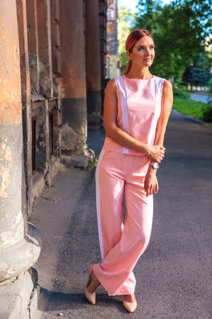 Young woman wearing pink suit posing on the street next to the old building