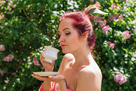 Red hair woman with cup of tea outdoors