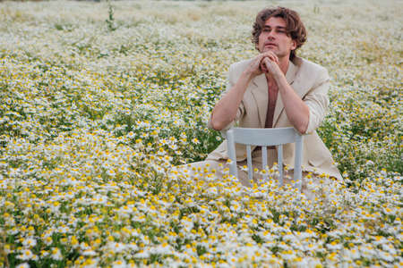 Tall handsome man dressed in a white suit on on body sitting on a white chair in camomile flowers field