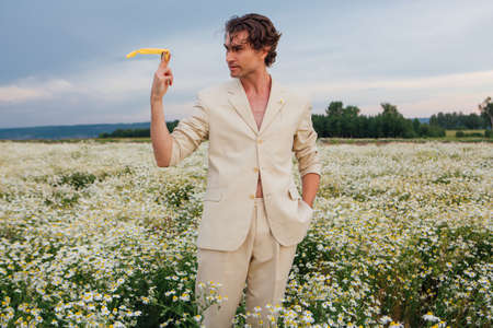 Tall handsome man dressed in a white suit on  body standing in camomile flowers field and posing with yellow plastic sunglasses