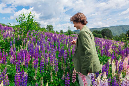 Tall handsome man in a green jacket standing on lupine flowers field, enjoing the beauty of nature. Man surrounded by purple and pink lupines.
