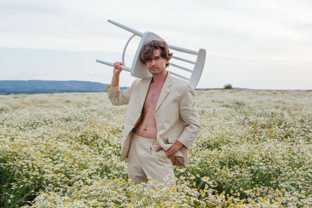 Tall handsome man dressed in a white suit, standing in the middle of camomile flowers field and holding white chair on his shoulder