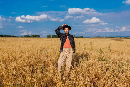 Rural Countryside Scene. Tall handsome man dressed in a black shirt and black hat standing at golden oat field. Summer landscape with blue sky