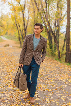 Tall handsome man dressed in a brown jacket walking with a bag on the autumn alley