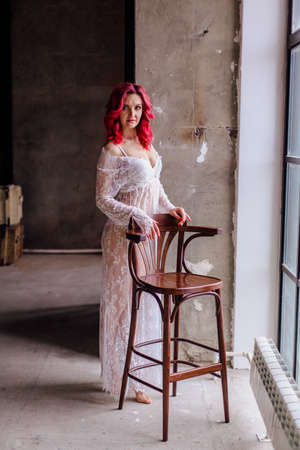 Attractive woman with pink hair in white light dress posing with high bar chair near large window. Lady in gentle lace peignoir sitting in a dark room with concrete floor and walls 版權商用圖片