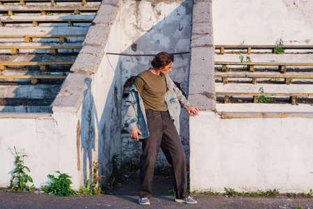 Fashion portrait of a tall handsome man dressed in jeans jacket on the crushed tribune of the old stadium during sunset