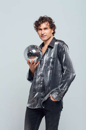 Portrait of tall attractive man with a mirror disco ball on a white background. Handsome man posing with a shiny disco ball in studio.