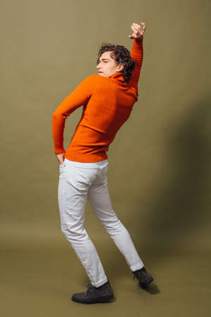 Tall handsome man dressed in orange turtleneck and white jeans posing on the green background Banque d'images