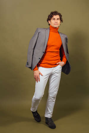 Full lengh portrait of a tall handsome man dressed in orange turtleneck, grey jacket and white jeans posing on the green background