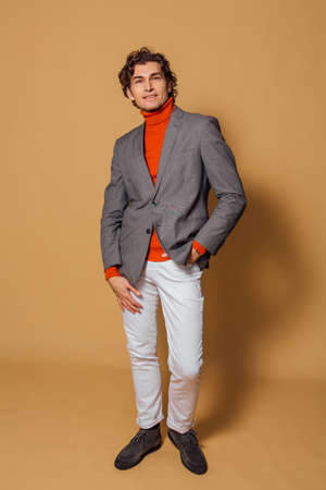 Fashion portrait of a tall handsome man dressed in orange turtleneck, white jeans and grey jacket posing on the beige background