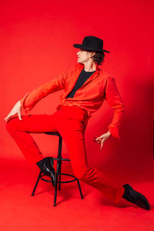 Portrait of a tall handsome man dressed in red shirt, red trousers and black hat posing with chair on the red background Stock Photo