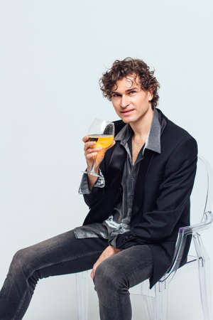 Tall handsome confident young man in a jacket sitting on the chair and holding glass of wine over white background
