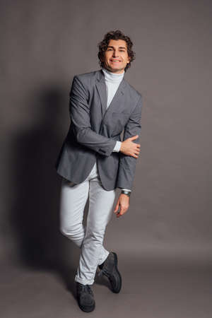 Fashion portrait of a tall handsome man dressed in white turtleneck, white jeans and grey jacket posing on the grey background