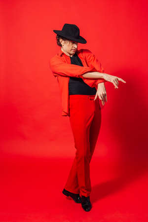 Portrait of a tall handsome man dressed in red shirt and black hat posing on the red background. Stock Photo