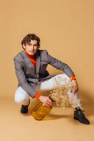 Fashion portrait of a tall handsome man dressed in orange turtleneck, white jeans and grey jacket sitting and holding vase with dry flowers on the beige background